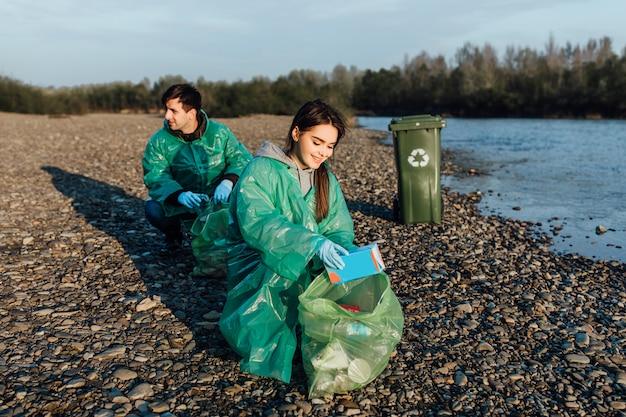 Jovens, limpeza de área de praia. conceito de voluntariado na praia.