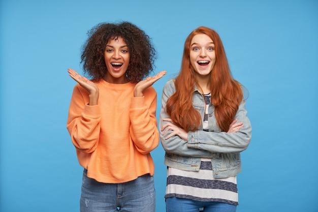 Jovens lindas amigas animadas olhando com alegria e mantendo a boca bem aberta, maravilhadas com algo enquanto posam sobre uma parede azul
