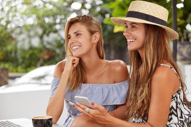 Jovens lindas e adoráveis com sorrisos positivos passam o tempo livre na cafeteria, usam tecnologias modernas e internet de alta velocidade para comunicação online e entretenimento. conceito de estilo de vida e lazer