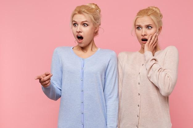 Jovens lindas gêmeas loiras espantadas com a boca bem aberta isolada sobre um fundo rosa apontavam para algo chocado