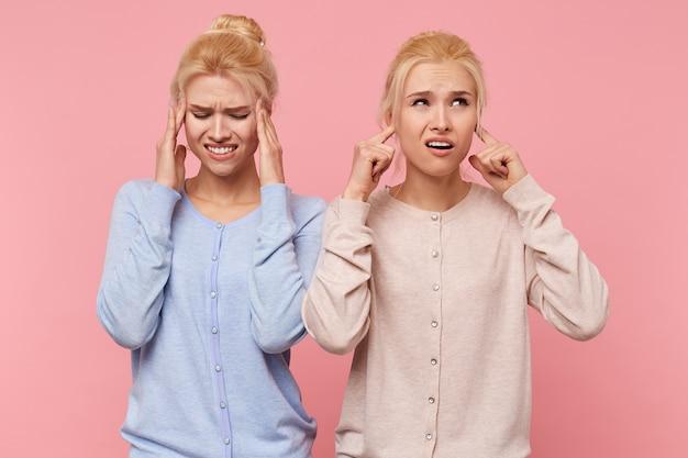 Jovens lindas gêmeas loiras ouviram um som desagradável do qual há um anel nas orelhas e uma cabeça se divide, isolada sobre um fundo rosa.