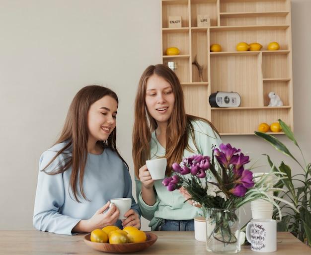 Jovens lindas irmãs segurando copos brancos
