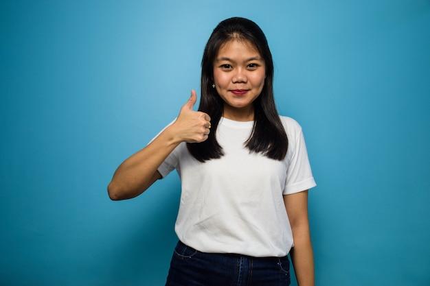 Jovens lindas mulheres asiáticas usando uma camiseta branca com fundo azul isolado gesto de polegar para cima