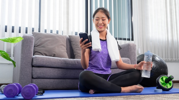 Jovens lindas mulheres asiáticas vestindo roupas esportivas de moda fazendo exercícios na esteira indoor de treinamento em casa, esporte e conceito de recreação.