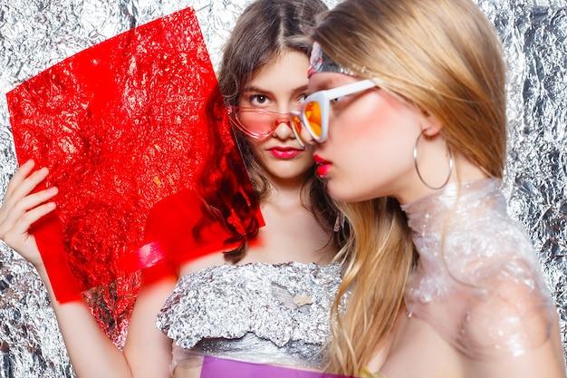 Jovens lindos amigos de duas meninas em fundo prata. mulher artística com estilo com maquiagem de fantasia. estilo vogue. criatividade. menina da moda. mulher do retrato da beleza. rosto de beleza com filtros de cores