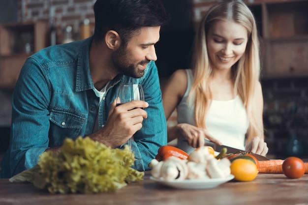 Jovens lindos estão conversando e sorrindo enquanto cozinham alimentos saudáveis na cozinha de casa