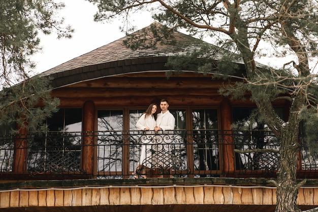 Jovens lindos recém-casados felizes apaixonados um homem e uma mulher em roupões de banho brancos na varanda da casa sorriem e se abraçam