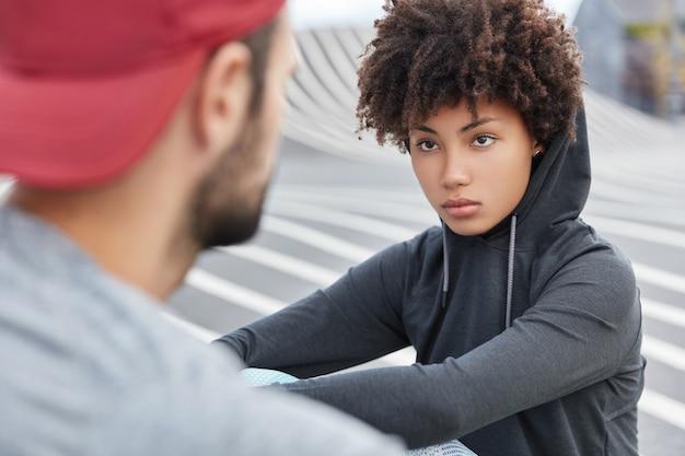 Jovens livres e independentes de capuz, olhem um para o outro com expressão pensativa, passem o tempo livre ao ar livre