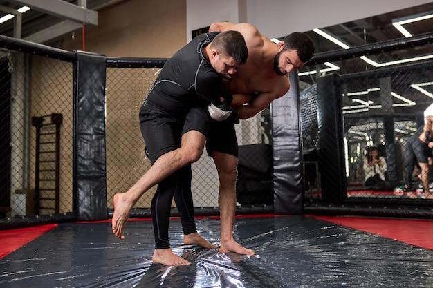 Jovens lutadores de boxe de mma lutam em lutas sem regras nos octógonos do ringue. artistas de artes marciais mistas durante a luta. conceito de esporte e boxe