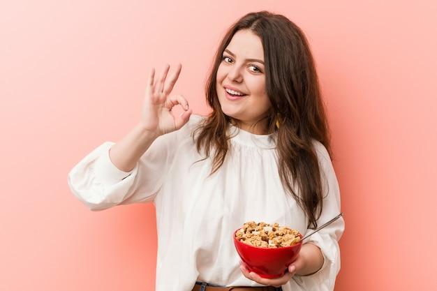 Jovens mais a mulher curvilínea do tamanho que mantém uma bacia de cereais alegre e segura mostrando o gesto aprovado.