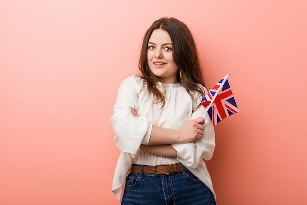 Jovens mais a mulher curvy do tamanho que mantém um sorriso da bandeira de reino unido seguro com braços cruzados.