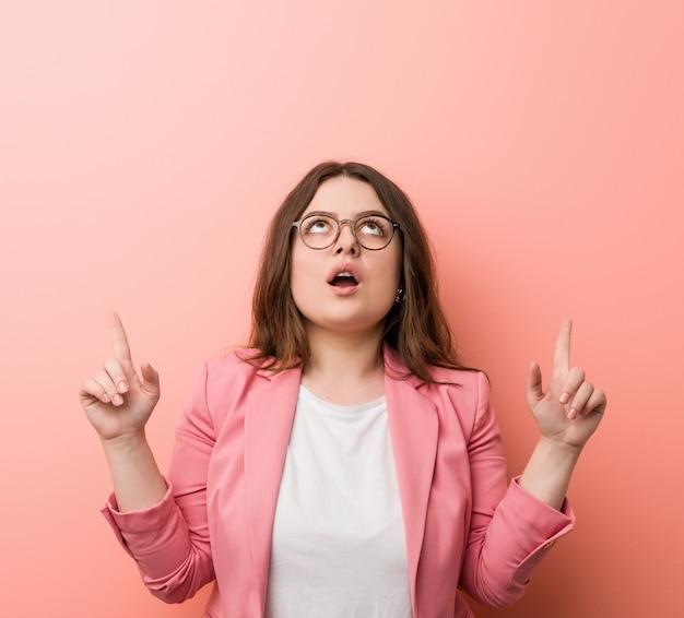 Jovens mais mulher caucasiana de negócios de tamanho, apontando de cabeça com a boca aberta.