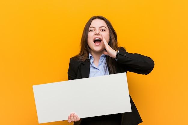 Jovens mais mulher curvy do tamanho que mantem um cartaz que shouting excitado para frontear.