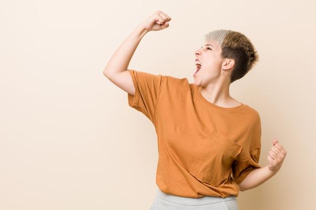 Jovens mais mulher tamanho com cabelo curto, levantando o punho após uma vitória, conceito de vencedor.