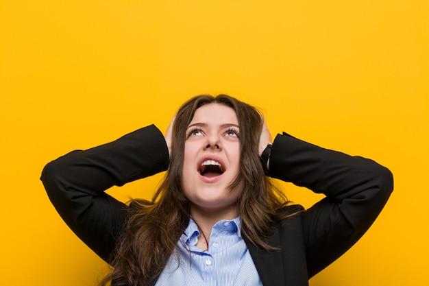Jovens mais tamanho mulher caucasiana, cobrindo os ouvidos com as mãos, tentando não ouvir som muito alto.