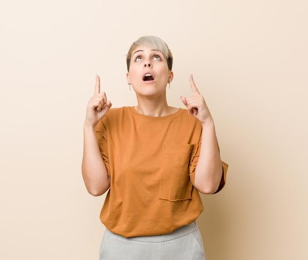 Jovens mais tamanho mulher com cabelo curto, apontando de cabeça com a boca aberta.