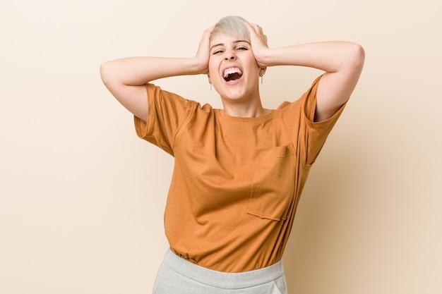 Jovens mais tamanho mulher com cabelo curto ri alegremente, mantendo as mãos na cabeça. conceito de felicidade.
