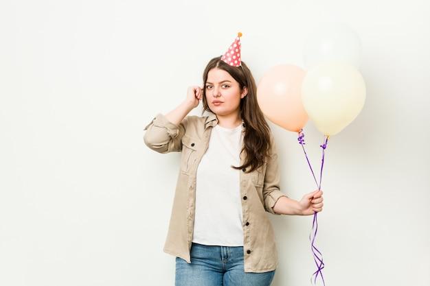 Jovens mais tamanho mulher curvilínea comemorando um aniversário apontando o templo com o dedo, pensando, focado em uma tarefa.