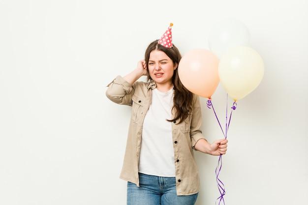 Jovens mais tamanho mulher curvilínea comemorando um aniversário cobrindo os ouvidos com as mãos.
