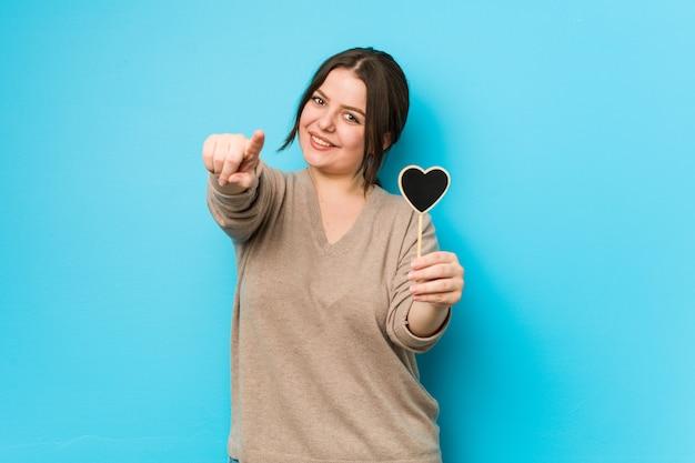 Jovens mais tamanho mulher curvilínea segurando um coração forma alegres sorrisos apontando para a frente.