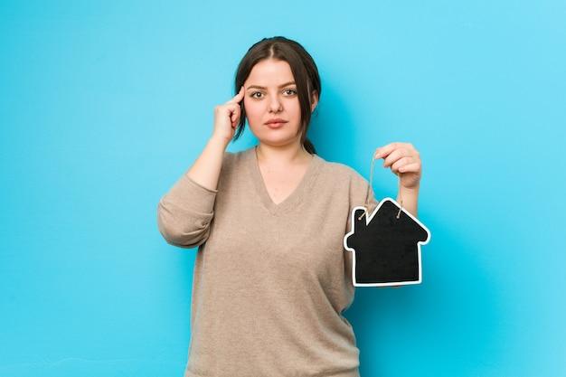 Jovens mais tamanho mulher curvilínea segurando um ícone em casa apontando seu templo com o dedo