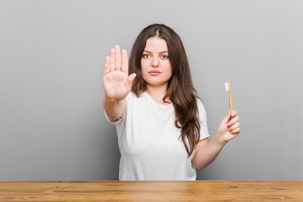 Jovens mais tamanho mulher curvilínea segurando uma escova de dentes em pé com a mão estendida, mostrando o sinal de stop, impedindo-o.