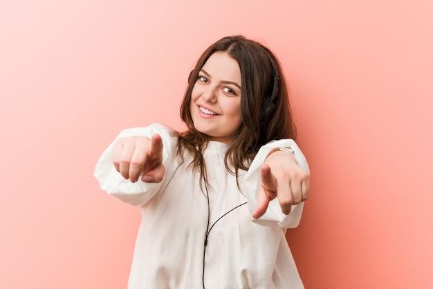 Jovens mais tamanho mulher curvy ouvir música com sorrisos alegres de fones de ouvido, apontando para a frente.