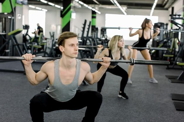 Jovens malhando com halteres no ginásio. mulheres atraentes e treinador de homem musculoso bonito estão treinando no ginásio moderno leve. linda garota agacha-se sob a supervisão do treinador.