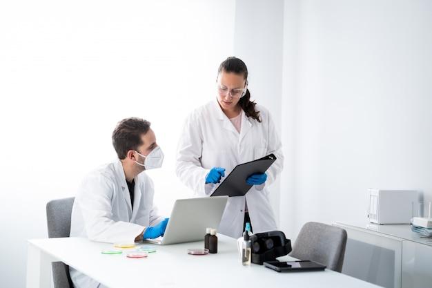 Jovens médicos do sexo masculino e feminino estão trabalhando no moderno laboratório de ciências biológicas e biotecnológicas