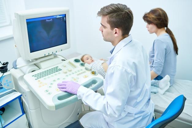 Jovens médicos exame criança pequena