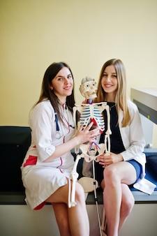 Jovens médicos se divertindo, posando com esqueleto.