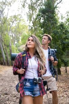 Jovens mochileiros, caminhadas, apreciando a vista e olhando a paisagem na floresta. viajantes atraentes caucasianos, caminhando no caminho na floresta. turismo de mochila, aventura e conceito de férias de verão