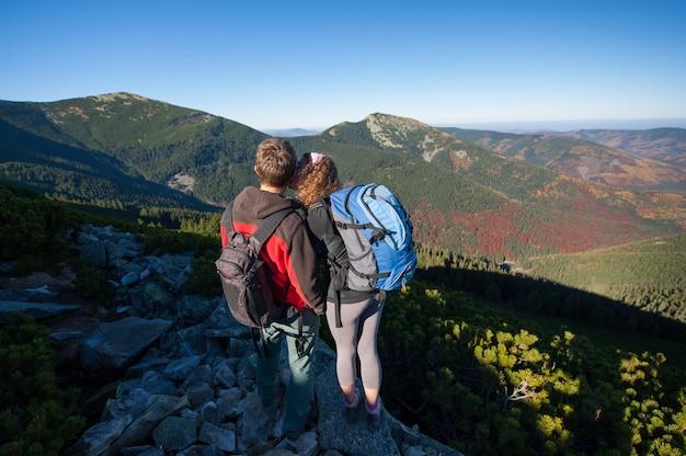 Jovens mochileiros casal apreciando a bela paisagem