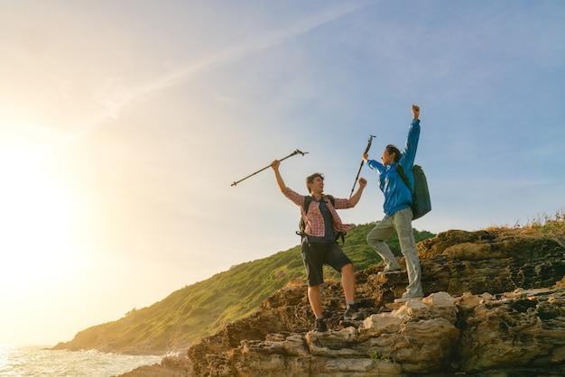 Jovens mochileiros, desfrutando de uma vista do vale do topo de uma montanha