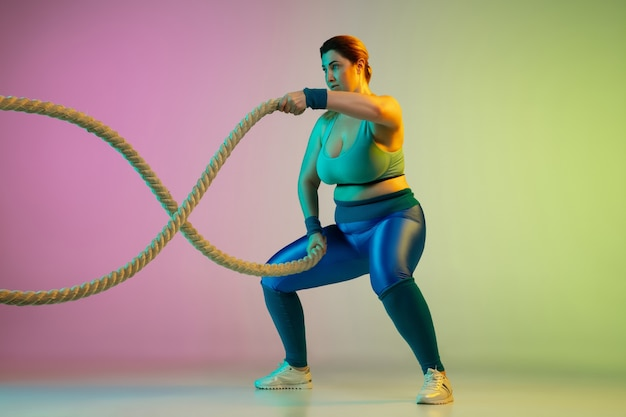 Jovens modelos femininas caucasianos plus size treinando na parede gradiente verde-púrpura