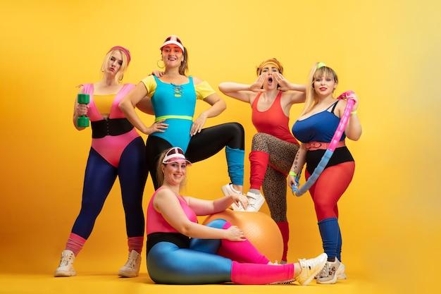 Jovens modelos femininas treinando na parede amarela