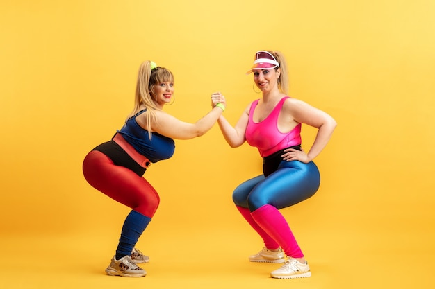 Jovens modelos femininos caucasianos plus size treinando na parede amarela
