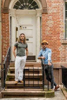 Jovens modelos masculinos posando ao ar livre nas escadas