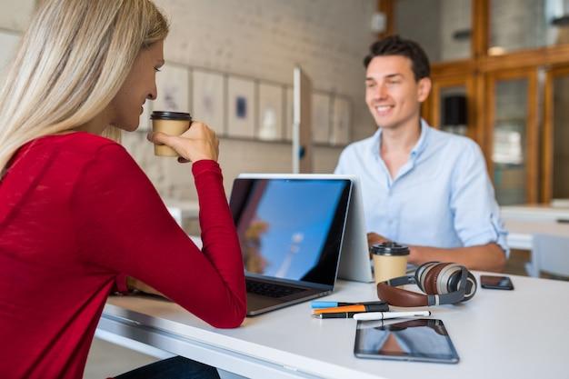 Jovens modernos sentados à mesa frente a frente, trabalhando em um laptop em um escritório colaborativo