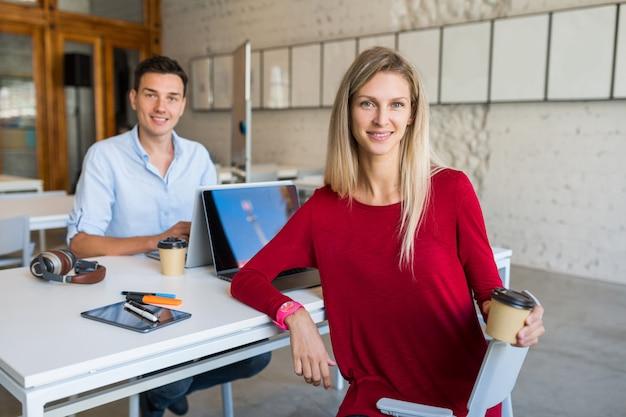 Jovens modernos sentados à mesa, trabalhando em um laptop em um escritório colaborativo