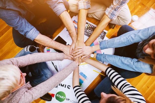 Jovens motivados funcionários sentados no chão do escritório no círculo e de mãos dadas juntos no meio.
