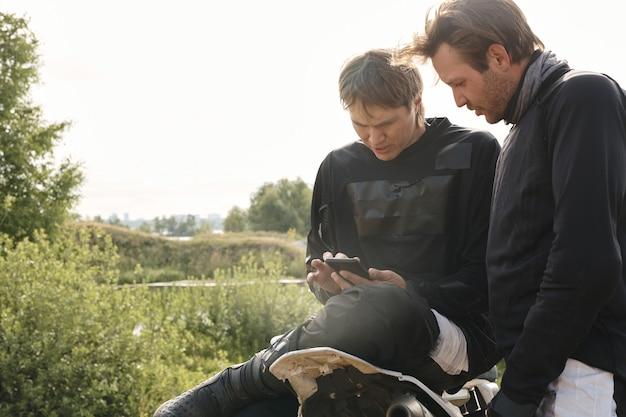 Jovens motociclistas concentrados em verificar a localização por meio de um aplicativo de smartphone enquanto dirigem off-road