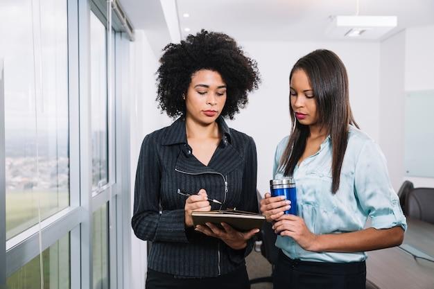 Jovens mulheres americanas africanas com copo de vácuo e documentos perto da janela