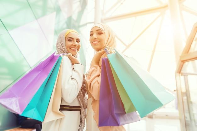 Jovens mulheres árabes com pacotes em pé