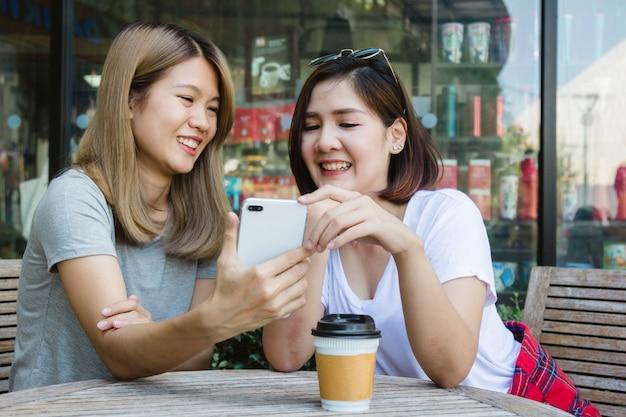 Jovens mulheres asiáticas alegres que sentam-se no café bebendo do café com amigos e que falam junto. attrac