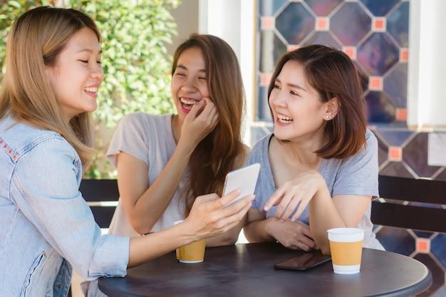 Jovens mulheres asiáticas alegres que sentam-se no café que bebe o café com amigos e que falam junto