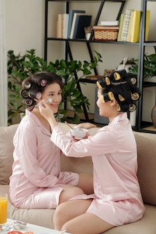 Jovens mulheres asiáticas aplicando máscara de argila no rosto umas das outras sentadas no sofá com rolos de cabelo