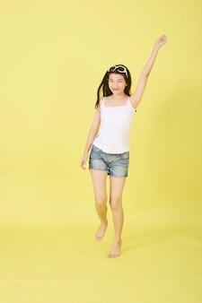 Jovens mulheres asiáticas bonitas com óculos de sol na cabeça a saltar sobre fundo amarelo