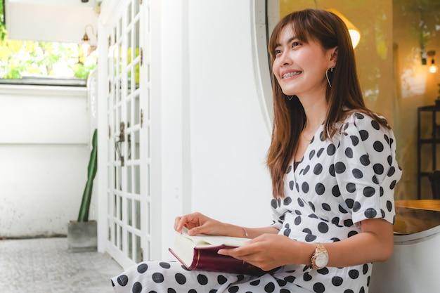 Jovens mulheres asiáticas bonitas que sentam o livro de leitura ao ar livre