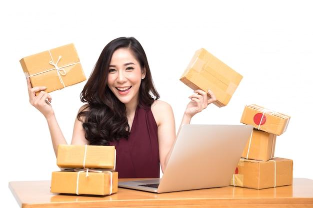 Jovens mulheres asiáticas com empreendedor de pequenas empresas de inicialização freelancer trabalhando em casa e animado com as ordens de muitos clientes, conceito de entrega de caixa de embalagem de marketing on-line